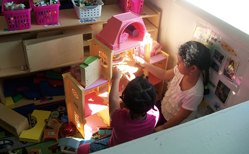 little girls playing with toy house at a Preschool & Daycare Serving Milton, DE, Frederica, DE, Harrington, DE, Dover, DE, Baltimore, MD